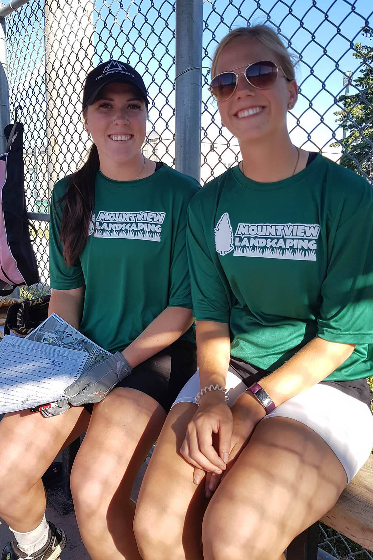 Two happy girls sitting on baseball dugout bench